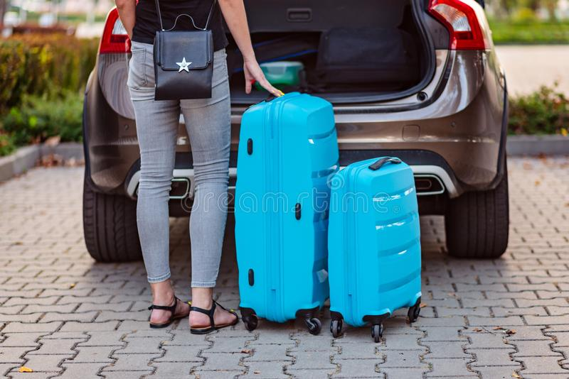 Woman putting two blue plastic suitcases to car trunk. stock photos