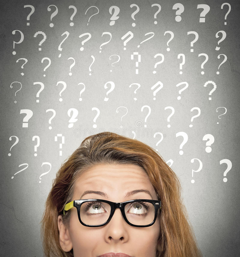 Woman with puzzled face expression and question marks above head. Headshot beautiful woman with puzzled face expression and question marks above her head looking stock photo