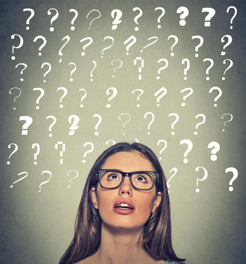 Woman with puzzled face expression question marks above her head looking up. Headshot young beautiful woman with puzzled face expression and question marks above royalty free stock photo