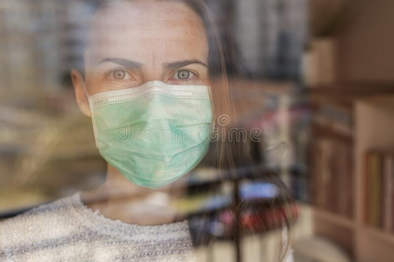 Woman in quarantine during coronavirus outbreak. Portrait of a woman standing inside her apartment, wearing medical face protection mask, in quarantine during stock photos