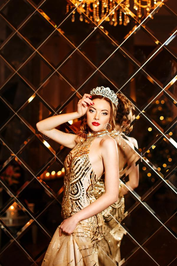 Woman queen princess in crown and lux dress, lights party background Luxury girl Long shiny healthy volume hair Waves Curls stock photos