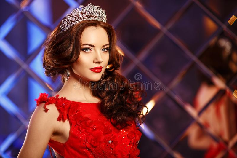 Woman queen princess in crown and lux dress, lights party background Luxury girl Long shiny healthy volume hair Waves Curls royalty free stock photography
