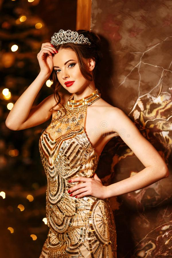 Woman queen princess in crown and lux dress, lights party background Luxury girl Long shiny healthy volume hair Waves Curls stock image