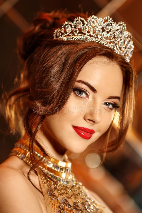 Woman queen princess in crown and lux dress, lights party background Luxury girl Long shiny healthy volume hair Waves Curls stock photo