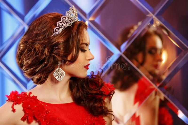 Woman queen princess in crown and lux dress, lights party background Luxury girl Long shiny healthy volume hair Waves Curls royalty free stock photos