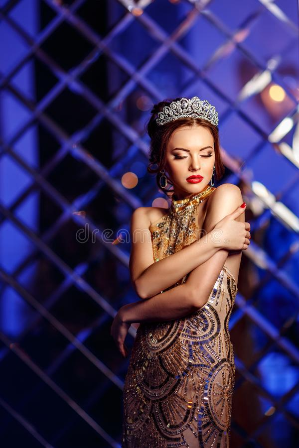 Woman queen princess in crown and lux dress, lights party background Luxury girl Long shiny healthy volume hair Waves Curls royalty free stock photo