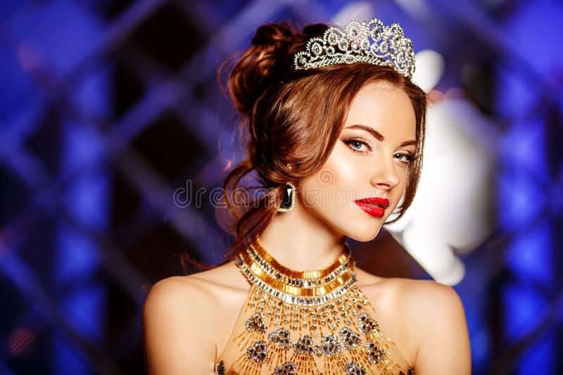 Woman queen princess in crown and lux dress, lights party background Luxury girl Long shiny healthy volume hair Waves Curls stock images