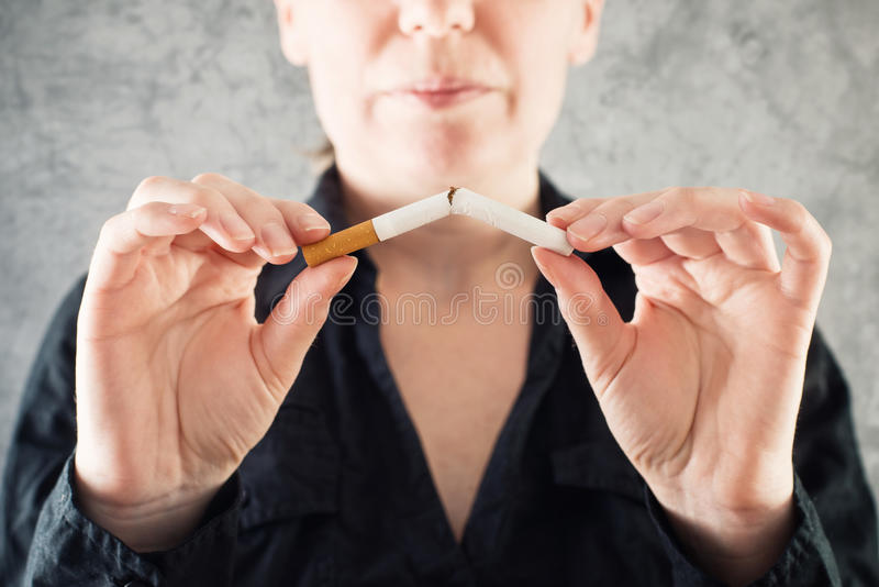 Woman quits smoking and breaking cigarette in half. Healthy lifestyle concept royalty free stock photo