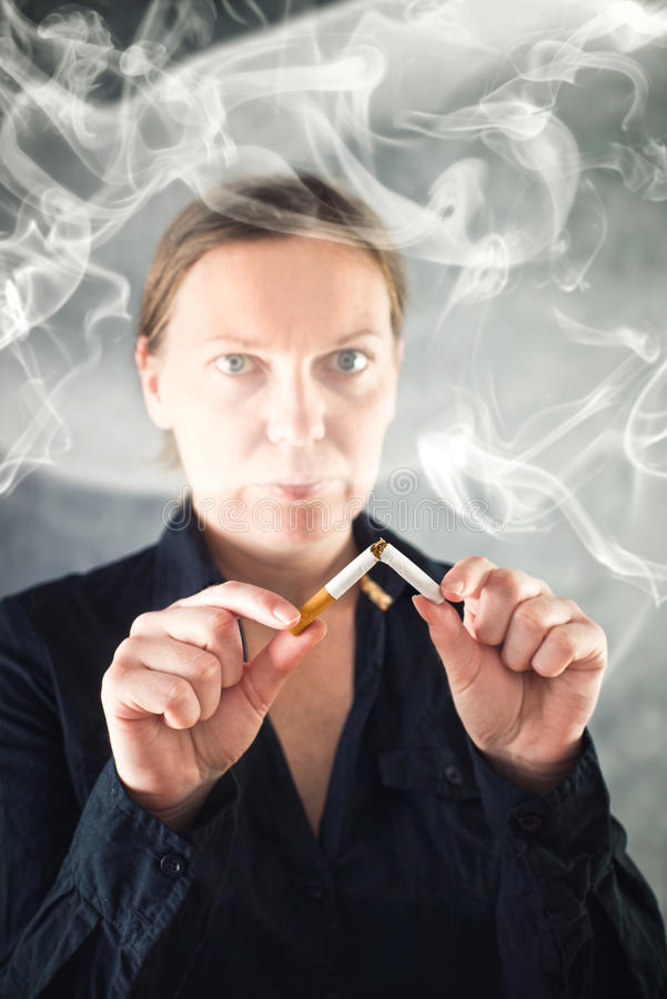 Woman quits smoking and breaking cigarette in half stock image