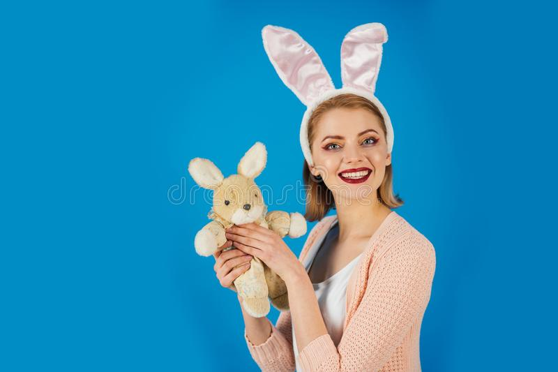 Woman in rabbit bunny ears. Egg hunt. Easter eggs as traditional food. Spring holiday. Girl with hare toy. happy woman. In bunny ears with toy. Happy easter royalty free stock images