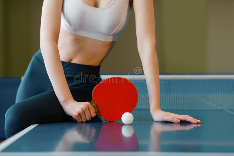 Woman with racket poses at the ping pong table. Woman with racket and ball poses at the ping pong table indoors. Female person in sportswear, training in table stock photography
