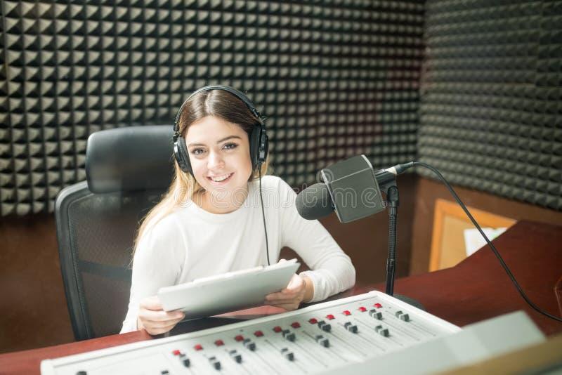 Woman radio broadcaster at recording studio. Portrait of pretty young woman radio broadcaster sitting in soundproof recording studio at radio station royalty free stock photo