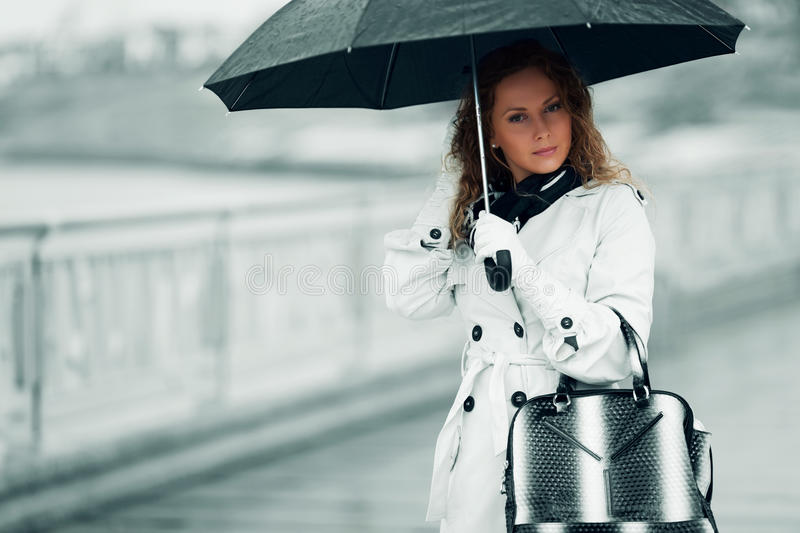 Fashion woman with umbrella walking in a city street royalty free stock photos