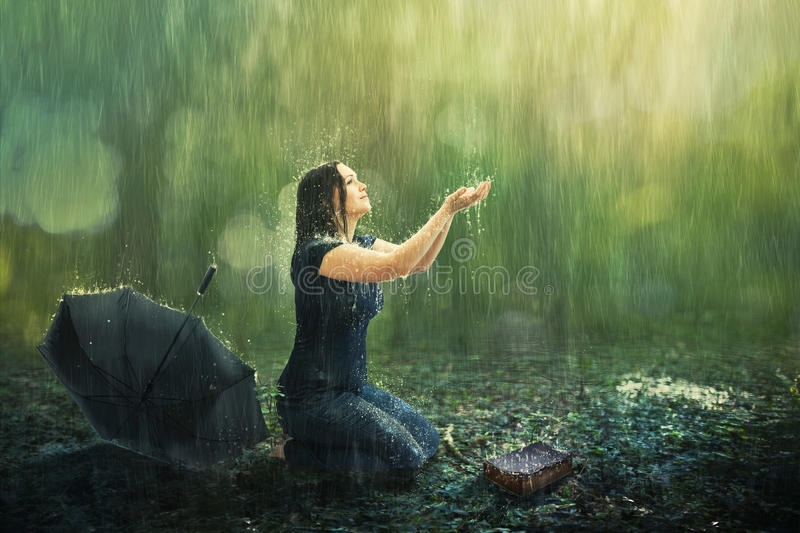 Woman and rain shower. A woman enjoys a rain shower in the forest