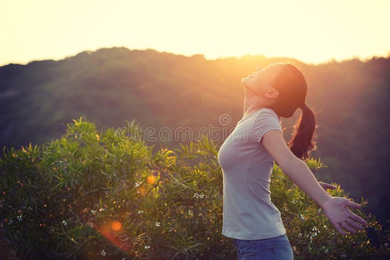 Woman raised arms to sunrise on mountain top in the moring. Freedom woman raised arms to sunrise on mountain top in the moring stock photography