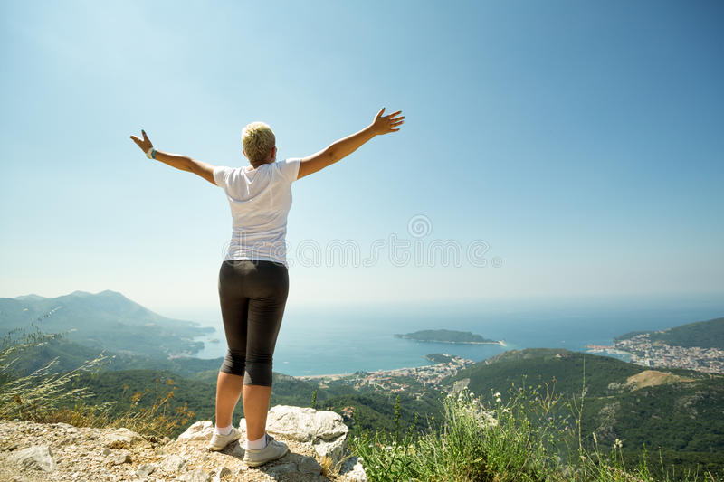 Woman with raised up hands enjoying sunny day royalty free stock photography