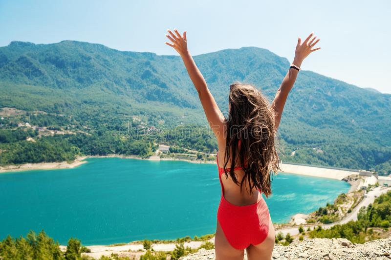 Woman with raised up hands standing on the top of rock stock images
