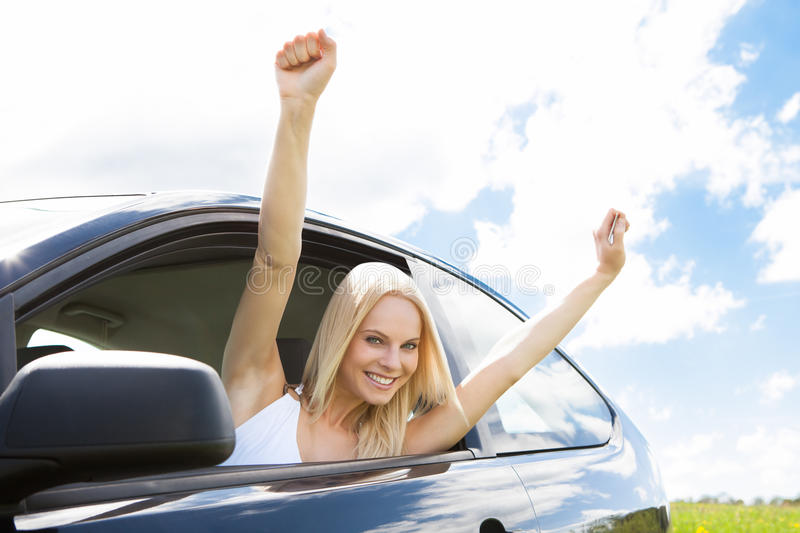 Woman raising hand out of car window royalty free stock images