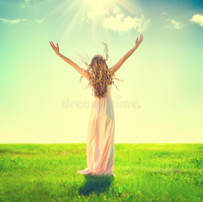 Woman raising hands in sunlight rays stock photo