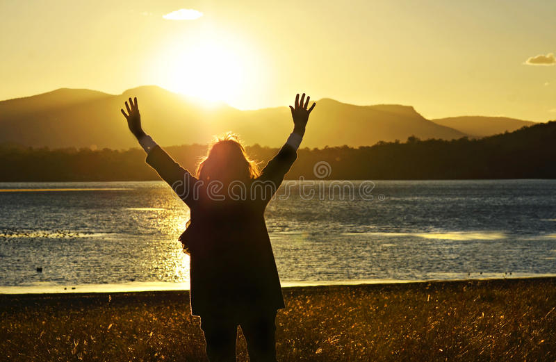 Woman raising hands worshiping praising praying God beautiful sunset stock photo