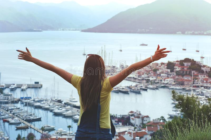 Woman Raising Her Hands Facing Cityscape Near Body of Water royalty free stock images