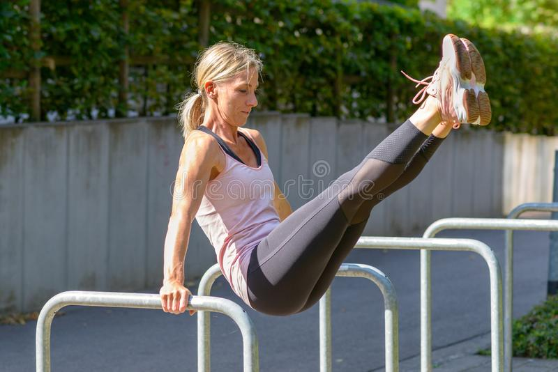 Woman raising legs from handstand on parallel bars stock photo