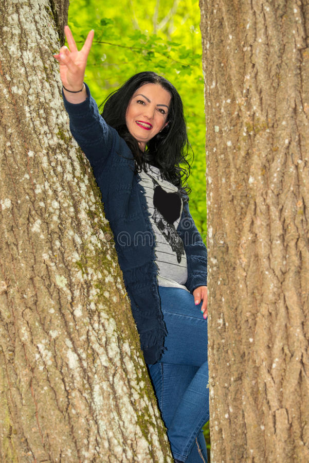 Woman ramped in the tree. Woman ramped between trees showing victory fingers sign royalty free stock photo