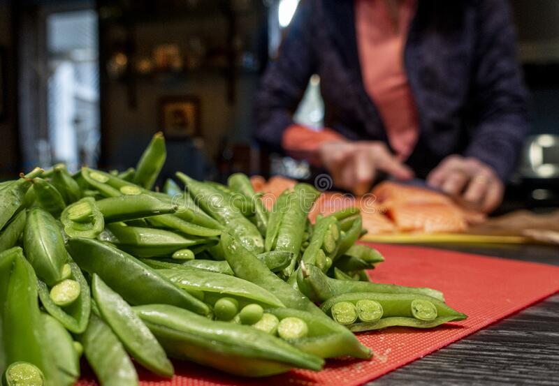 Woman with raw salmon and pea pods royalty free stock image