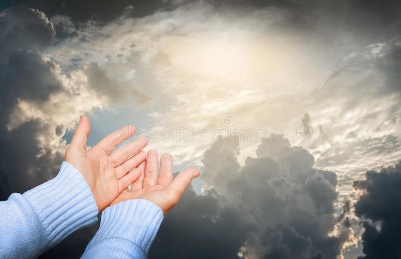 Woman reaches out to the sky during prayer. Sky with dark, dramatic clouds, through which the sun looks_. Woman reaches out to the sky during prayer. Sky with royalty free stock images
