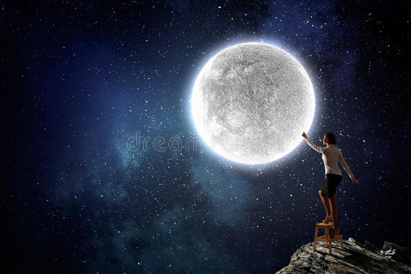 Woman reaching hand up. Businesswoman standing on chair and reaching hand to touch moon stock image