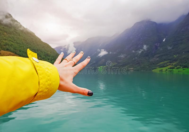 Woman reaching out hand near the beautiful mountain lake. royalty free stock images