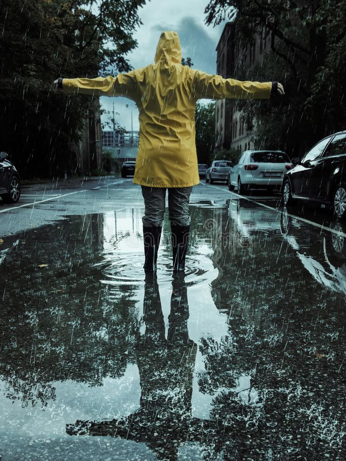 Woman reaching out her arms on a rainy day in autumn stock photography