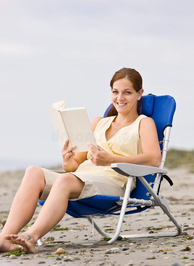 Woman reading book at beach royalty free stock photography