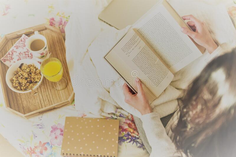 Woman reading book in bed stock photos