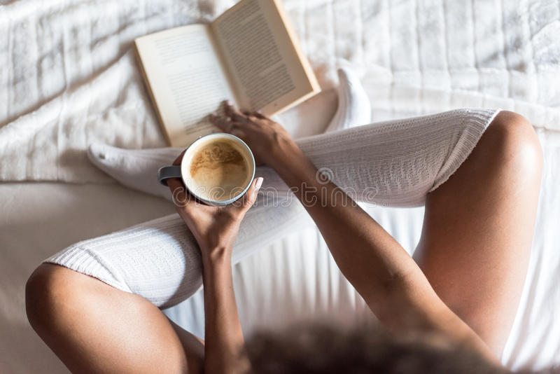 Woman reading a book and drinking coffee on bed with socks royalty free stock image