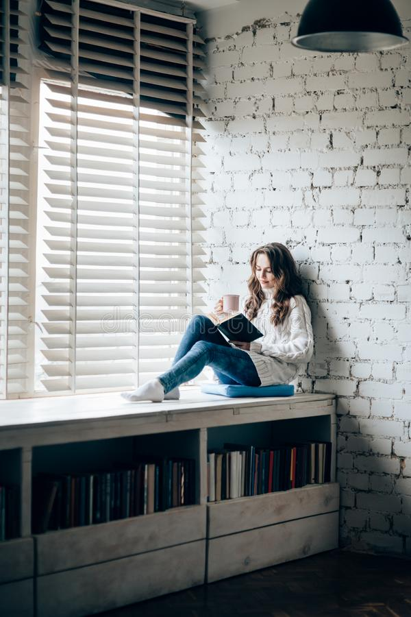 Woman reading book and drinking hot coffee sitting on window sill. At home. Relax concept stock photography