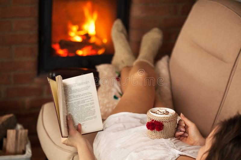 Woman reading a book and enjoying a hot chocolate by the fire stock images