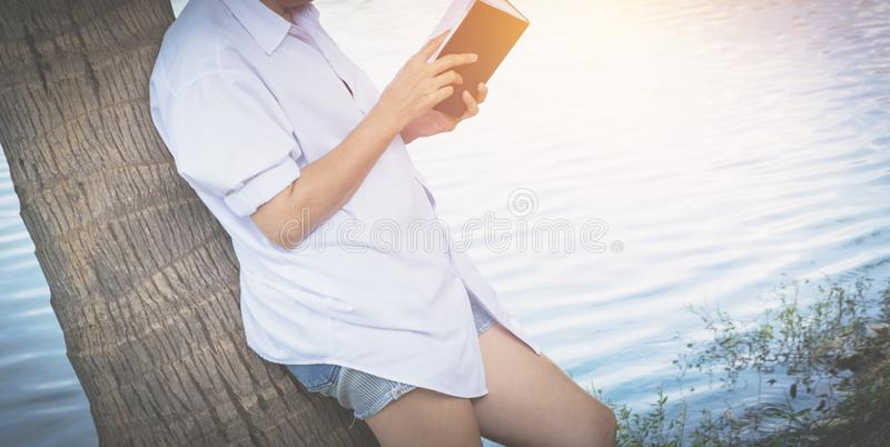 Woman reading a book enjoys of rest. Woman hand holding a book stock photos