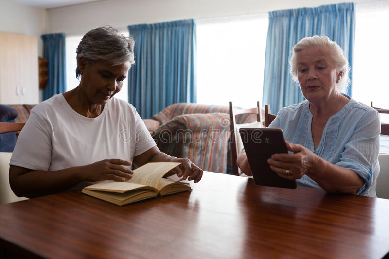 Woman reading book while friend using tablet at table royalty free stock photo