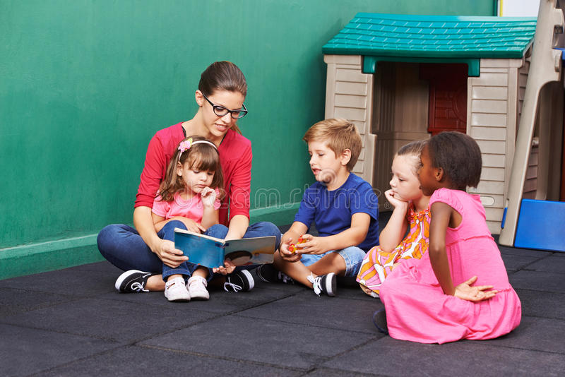 Woman reading book for group of children stock images