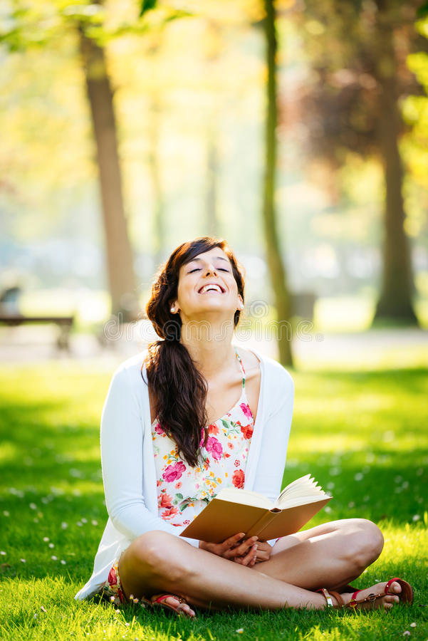 Woman reading book and having fun in park stock photo
