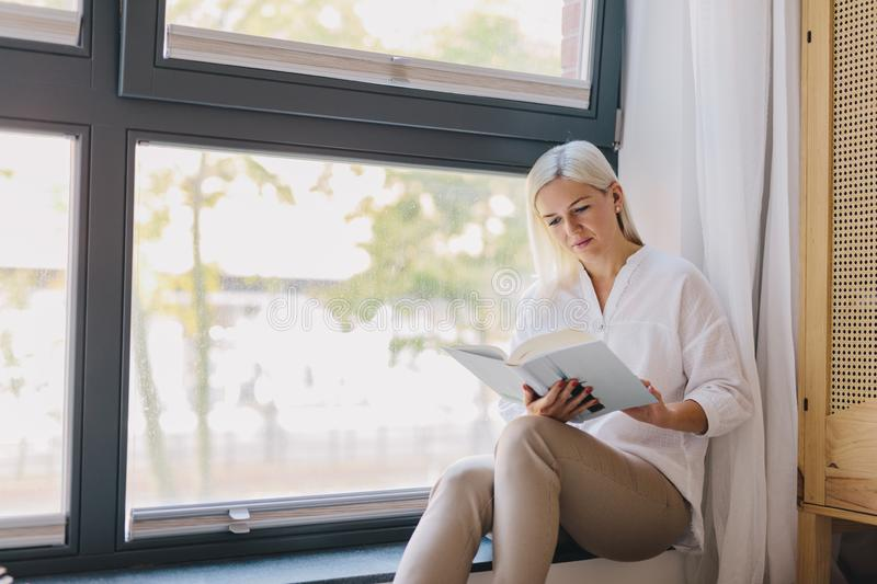 Woman reading book at home by the window royalty free stock image