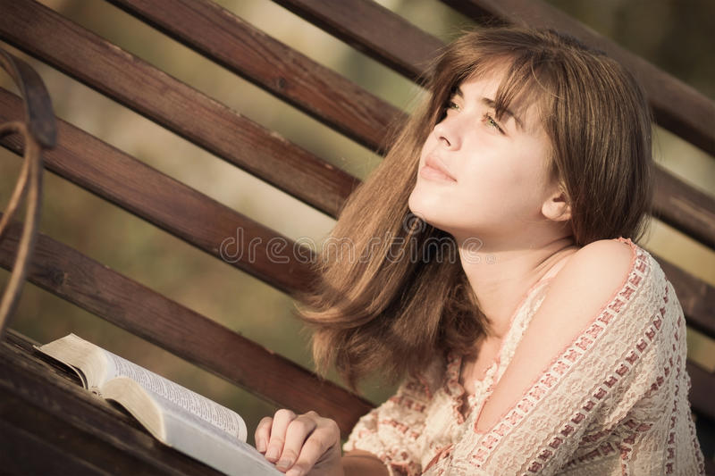 Woman reading a book lying on the bench stock images