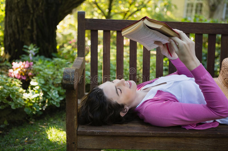 Woman reading a book while lying on a bench stock photos