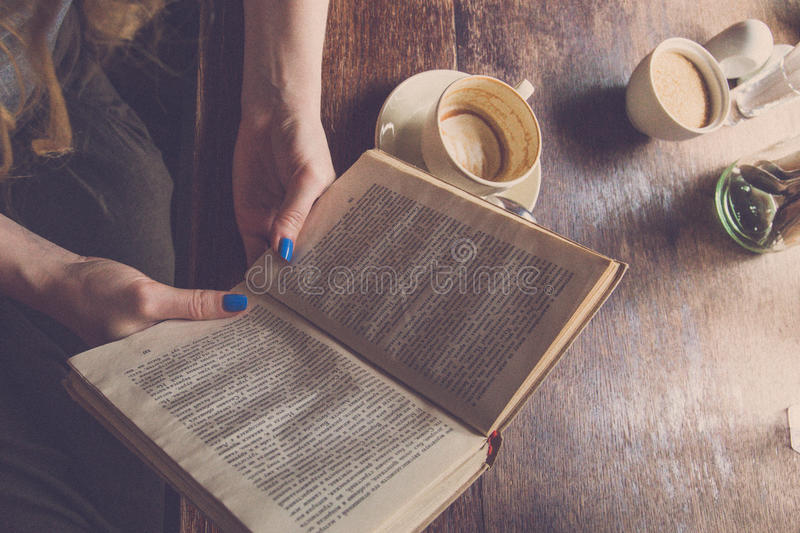 Woman reading book in the morning and drinking coffee royalty free stock images