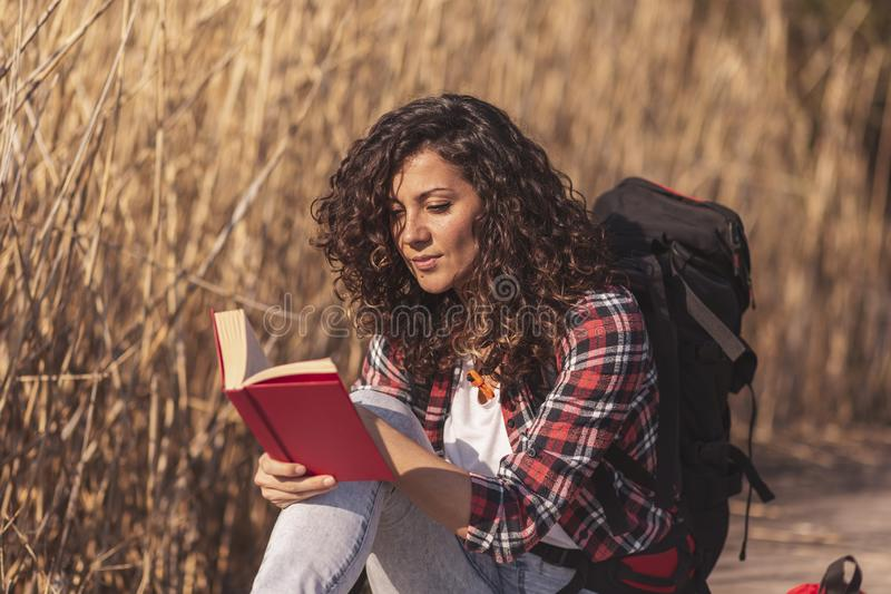 Woman reading a book in nature. Beautiful young woman sitting on the wooden lake docks, enjoying a beautiful autumn day in nature and reading a book stock photos