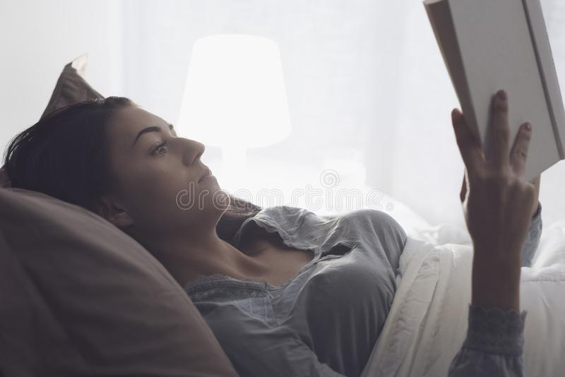 Woman reading a book at night royalty free stock photos
