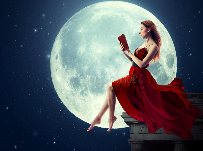 Woman reading book over full moon royalty free stock photography