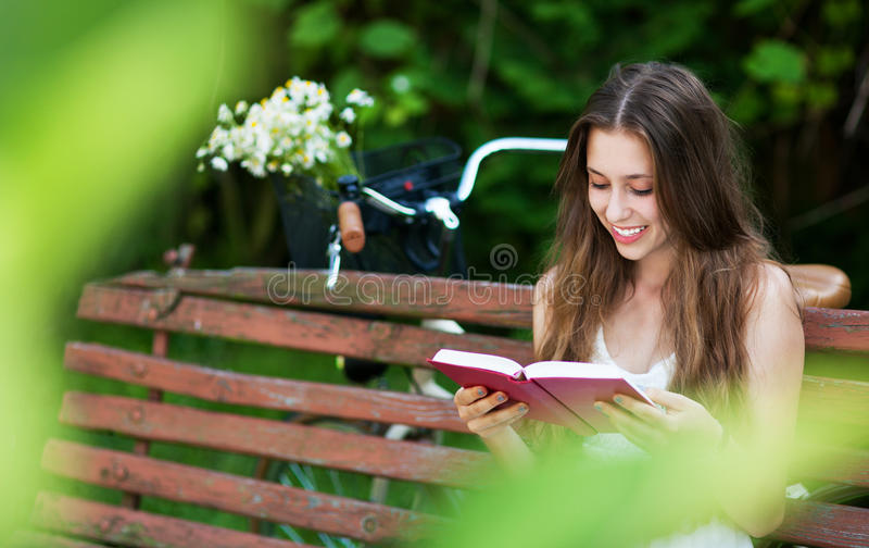 Download Woman Reading Book On Park Bench Stock Photo - Image: 25780506