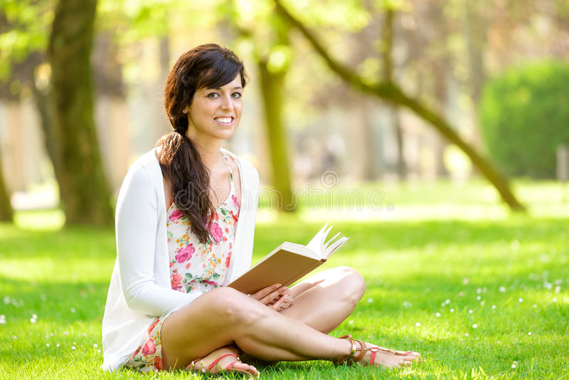 Woman reading book in park stock images
